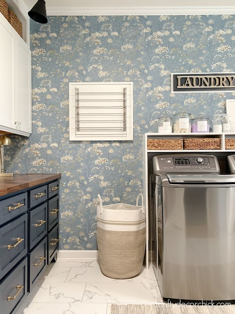 laundry room with floral wallpaper and hanging drying rack