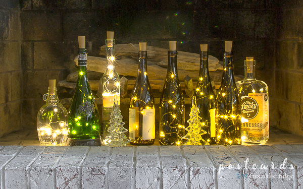wine bottles with fairy lights inside a fireplace