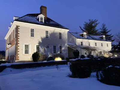 Side of two-story mansion with stuccoed wall. There is snow on the ground and floodlights cast shadows on the wall of the building.