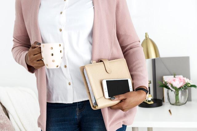 Mulher de negócios negra segurando agenda e celular em uma mão e uma cena em outra