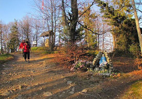 Zielony szlak odchodzi ze szczytu obok miniaturowej groty z figurą Matki Boskiej.
