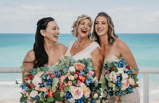 Bride with Bridesmaids laughing holding bouquets