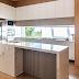 Cozinha branca, cinza e amadeirada com ilha em porcelanato e janela entre bancada e armário!