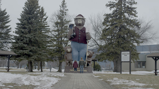 a man and a woman and a smokey the bear statue