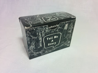 The box, about 3 centimetres by 7 centimetres by 5 centimetres, with the game Tell Me a Story. The box is black with various white line drawings all over it, and a large speech balloon with the title n the front and the lid.