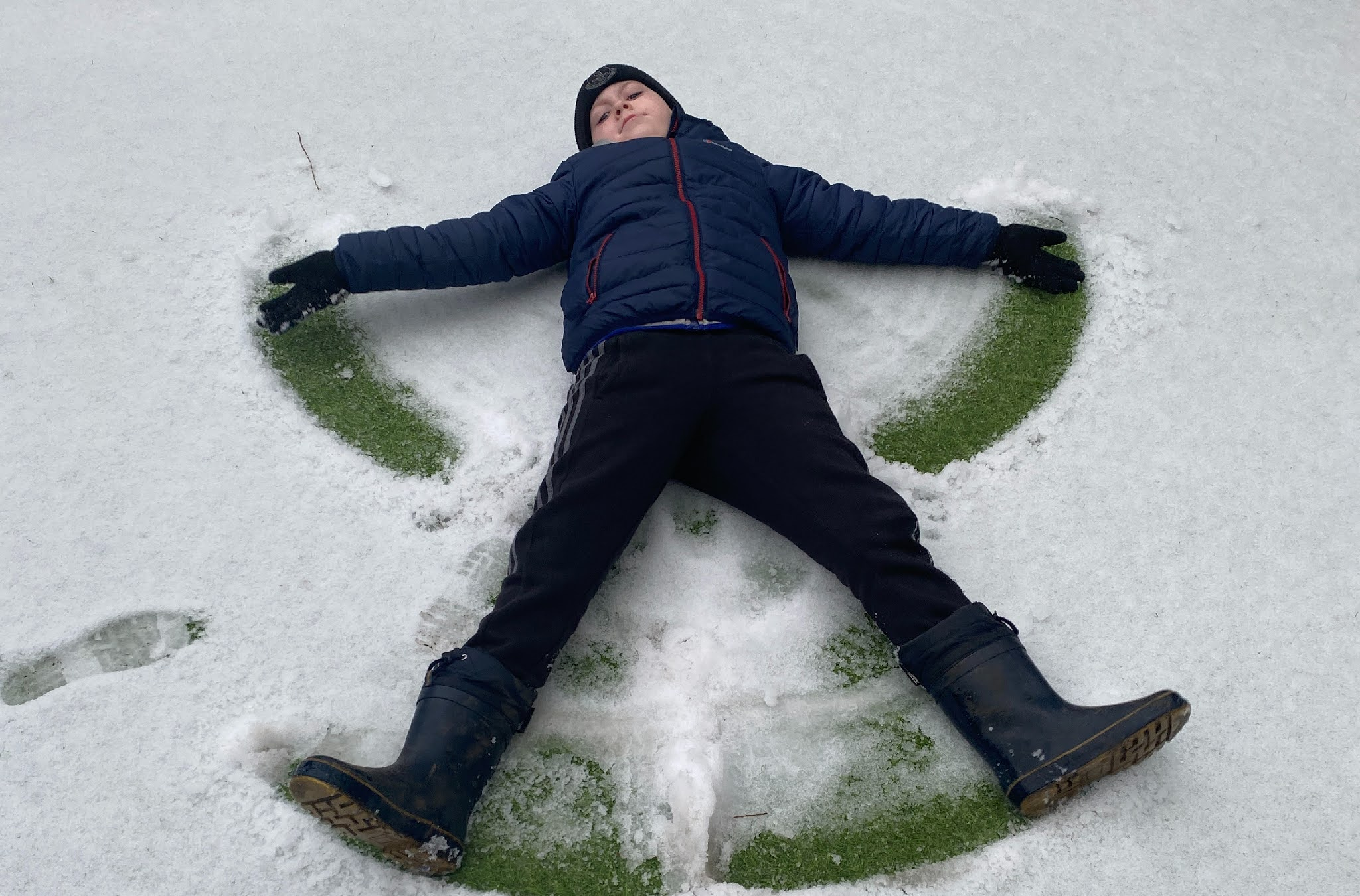 a boy making a snow angel in the snow