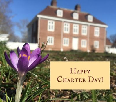"""Two-story brick manor house at Pennsbury Manor in background with a purple crocus up close to camera. Text reads """"Happy Charter Day!"""""""