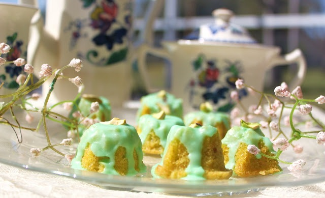 Little pistachio tea cakes with frosting, flowers on a antique plate