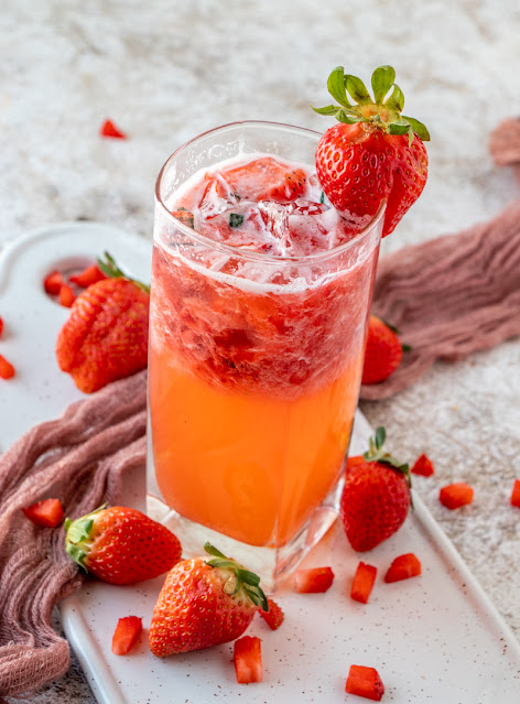 Drink in a glass with strawberries and a brown towel