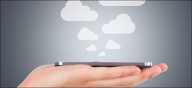 يد تمسك هاتفًا مع ظهور السحب ، مما يرمز إلى حفظ الملفات في السحابة.