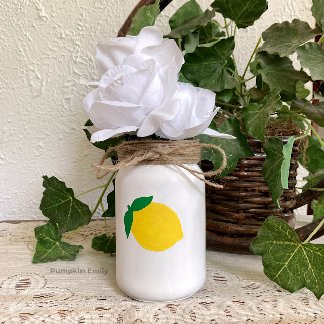 A lemon painted on a jar and with twine wrapped around the top of it.