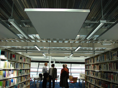 A small group of people, seen from behind, standing between bookshelves in a library, under a large white suspended sound dampening board.