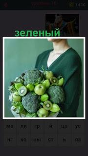женщина в зеленой кофте с зелеными яблоками и капустой