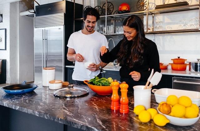 couple happily preparing salad