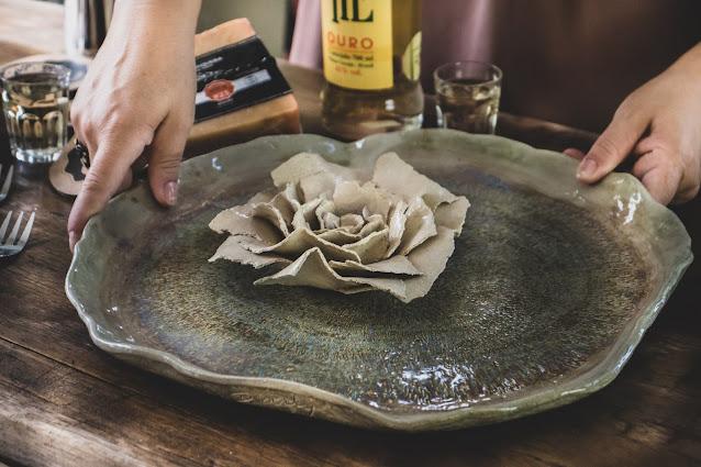 Prato e flor de cerâmica sendo colocado na mesa para refeição