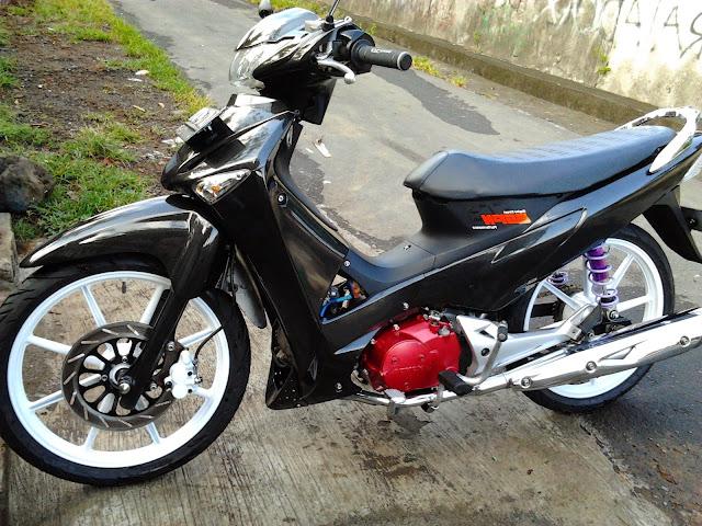 Foto Modifikasi Honda Kharisma bergaya Minimalis yang didominasi warna hitam pekat velg berwarna putih dengan ukuran 17 inci bagian knalpot dilabur warna merah menggunakan knalpot racing sepasang spion
