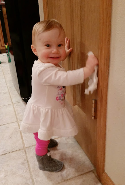 my one-year-old daughter wipes up a door with a huge smile on her face