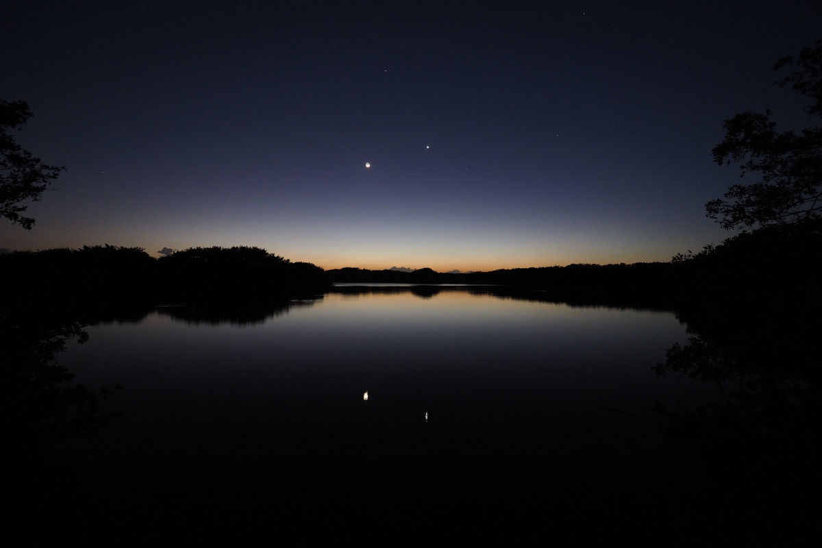 The morning star Venus and the moon over a shining lake in Florida.