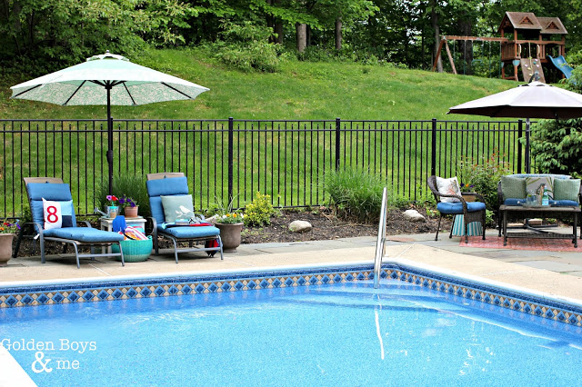 Outdoor pool and patio ideas with black aluminum fence and in-ground vinyl lined pool  - www.goldenboysandme.com