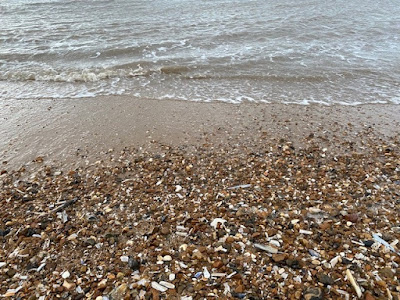 Pebbles and stones on a sandy beach with waves coming in