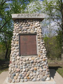 "a bronze plaque with information about Theophile Bruguier is mounted on a stone pillar with the name ""Bruguier"" carved into it."