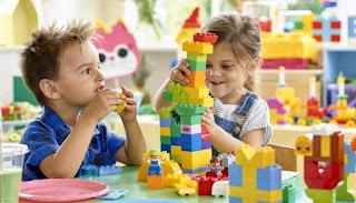 duas crianças brincado com peças Lego