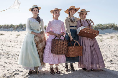 "In Greta Gerwig's ""Little Women"" (2019), the March sisters Meg, Amy, Jo, and Beth (Emma Watson, Florence Pugh, Saoirse Ronan, and Eliza Scanlen) stand on the beach together with baskets for a picnic."