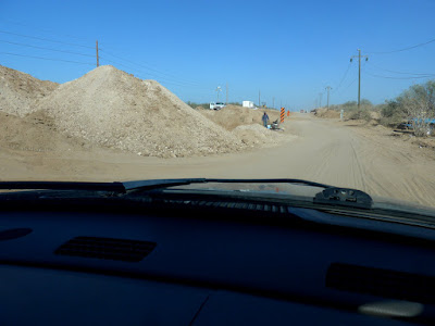 Driving in the ditch while the road is being built.