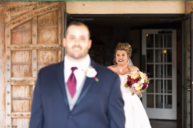"""Cassie and Wyatt tied the knot at The Palace Event Center, in Yukon, OK, on July 15, 2017.   The venue's magnificent wood entry doorways, outside rock façade, and adjacent country landscape provided the perfect backdrop to photograph the first look and pictures of the jovial wedding party.  The venue was spacious, which allowed us to sneak in a few pre-dressed shots of the girls in their """"Wedding Tribe"""" t-shirts.     Cassie's elegant, form-fitting, strapless, satin wedding dress overlaid with lace and sequins looked like it was made especially for her.  Wyatt was quite the Knight in Shining Armor dressed in his navy suit, grey vest, and burgundy tie.  The four beautiful bridesmaids wore matching full-length, flowing, burgundy gowns, slit at the knee.  Cassie's gorgeous bouquet was composed of baby's breath, peonies and ranunculus in rich hues of vibrant burgundy, red, pink, burnt orange, and yellow gold.  To add to the excitement of the day, their son had a special assignment—carrying the sign down the aisle that stated, """"Daddy, Here Comes Our Girl.""""     The venue's grand ballroom, with it's beautiful chandeliers and romantic lighting, was the perfect backdrop for the couple's reception.  Candlelight, flowers, and twinkle lights adorned the nuptial stage, and after the vow exchange, Cassie and Wyatt participated in their first dance.  Guests were invited to enjoy the buffet, the cutting of the cake, and the toasts by the best man and bridesmaid.  Chairs were quickly removed from the dance floor, and while almost everyone spent the rest of the afternoon relaxing, dancing and socializing, there was a particularly fun-loving group of guests who decorated the bride and groom's Jeep with sayings, crepe paper, and a car filled-to-the-brim with balloons!        Cassie stated that the best part of the wedding was being able to see so many family and friends at the reception having fun and enjoying themselves.  She said, """"If we had it to do over, we wouldn't do anything diff"""