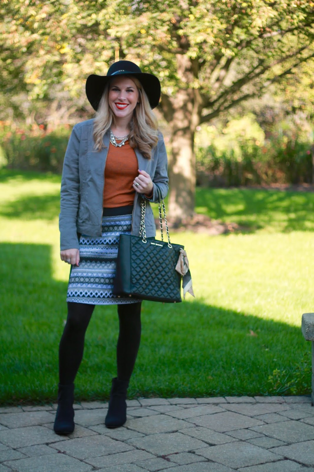 grey jacket, grey jacquard skirt, rust tee, black floppy hat, sock booties, black quilted leather tote