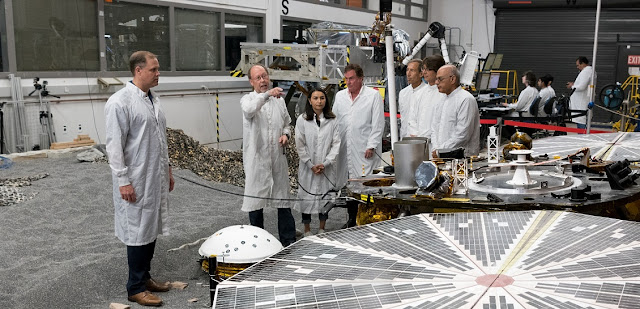 NASA Administrator James Bridenstine (left) discusses the agency's next Mars landing mission in the In-Situ Instrument Laboratory where an engineering model of the InSight is being tested at NASA's Jet Propulsion Laboratory, Pasadena, California. InSight is currently on its way to Mars. On Nov. 26, 2018, it will touch down in Mars' Elysium Planitia region, where it will be the first mission to study the deep interior or the Red Planet. InSight stands for Interior Exploration using Seismic Investigations, Geodesy and Heat Transport.  To the right of Bridenstine, from left to right, are JPLers Bruce Banerdt, InSight principal investigator; Marlene Sundgaard, InSight systems engineer; Michael Watkins, director of JPL; Larry James, deputy director of JPL; Jakob van Zyl, JPL director for solar system exploration; and Keyur Patel, JPL deputy director for solar system exploration. The decagonal object in the foreground is a mockup of one of two solar arrays on the InSight lander. The white-domed object at the administrator's feet is a mockup of SEIS, a seismometer which will record quakes on Mars. Image credit: NASA/JPL-Caltech