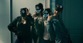 4 women wearing scary paper masks