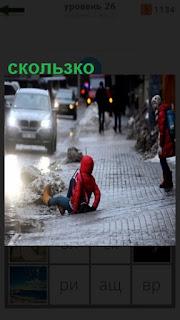 человек упал на землю, так скользко зимой на дороге
