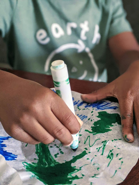 African American child using green marker to color coffee filter for Earth Day craft