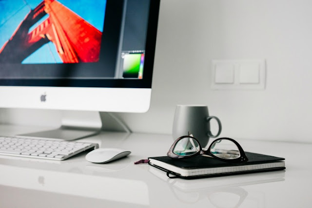 Surprise Yourself - Start Blogging | Morgan's Milieu: Mac on a white desk, glasses sitting on top of a notebook.