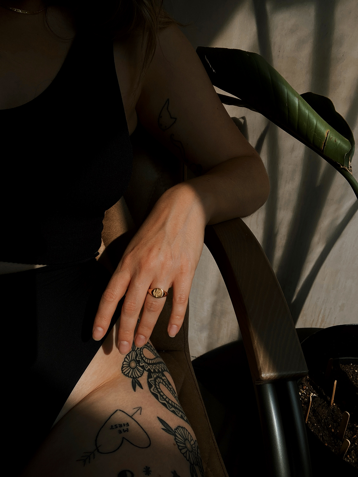 Cropped shot of Lyzi sitting on a vintage chair in dramatic shade and sunlight shining on tattoos and Daisy London forget me not signet ring.