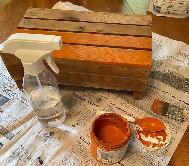 Photo of a small crate being painted orange