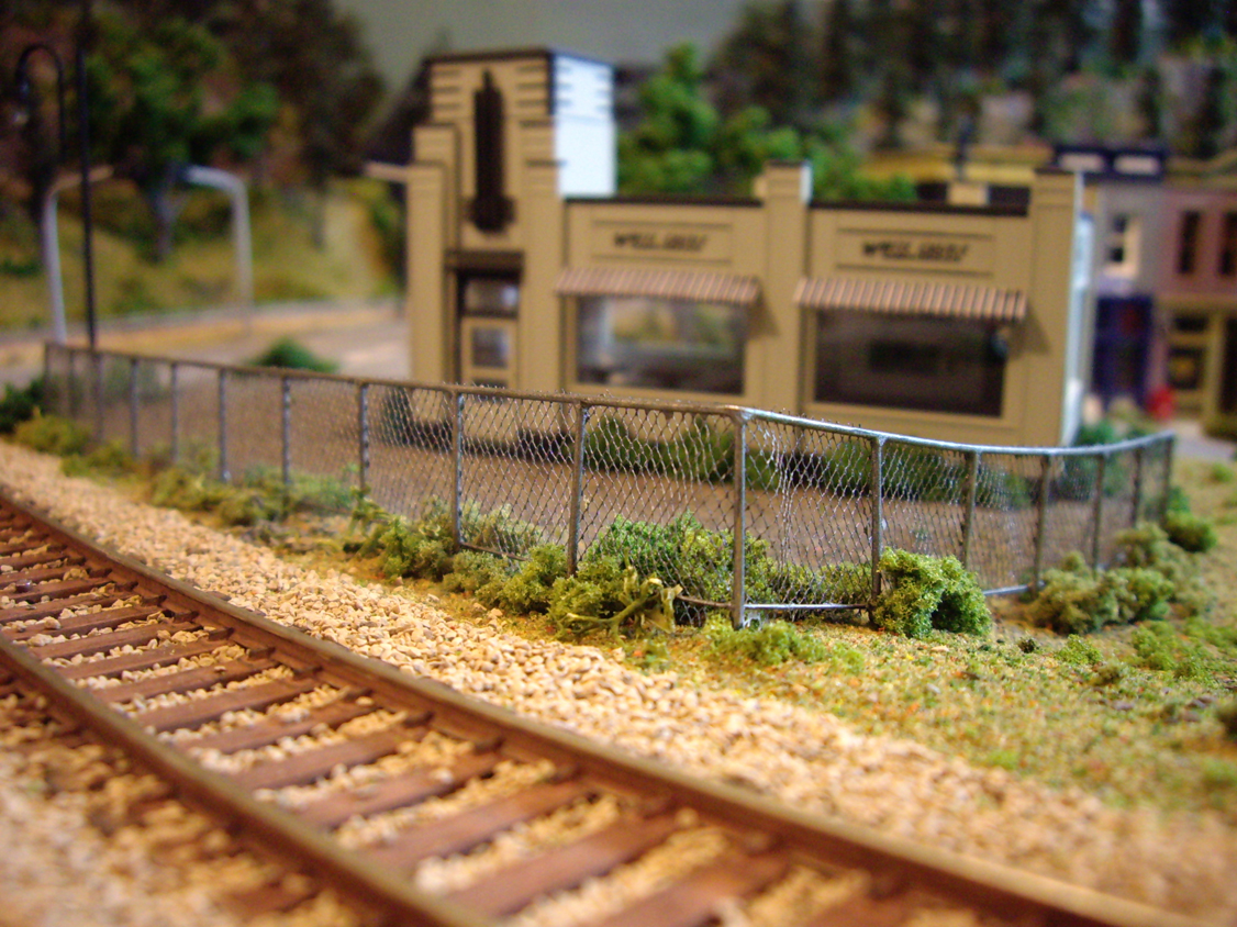 A scratch built chain link fence installed between railroad track and an Atlas White Castle kit