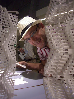 male artist with cut and folded paper art