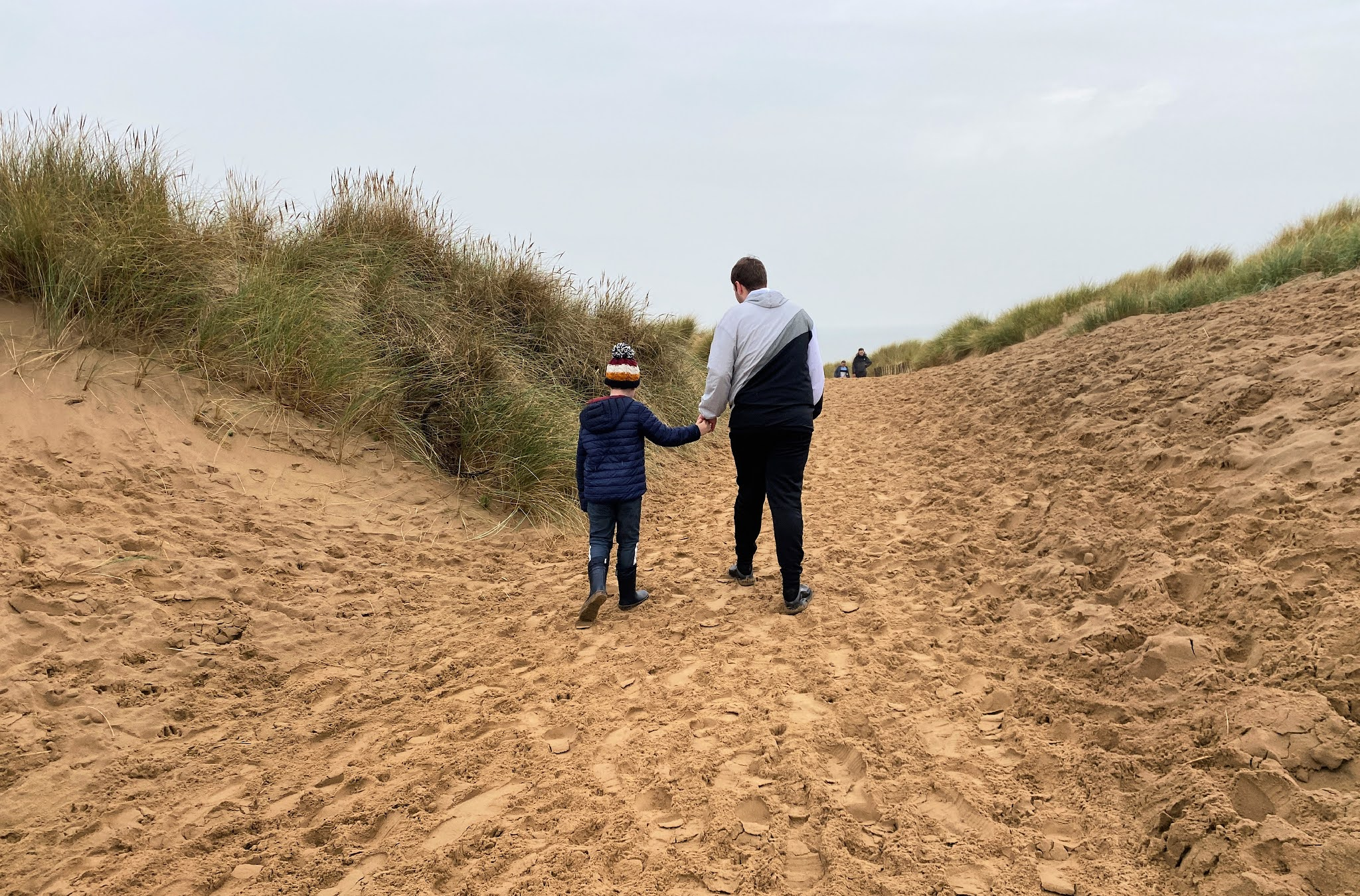 two boys walking over sand dunes
