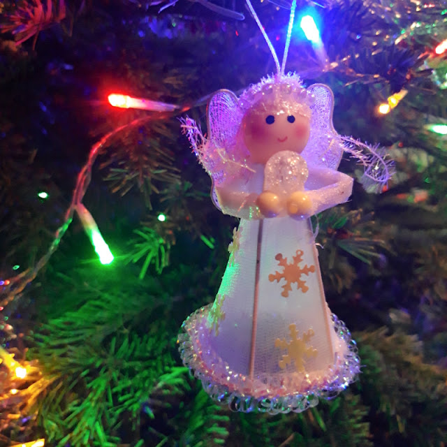 An angel decoration sits amid the pine needles of a Christmas tree, surrounded by coloured fairy lights