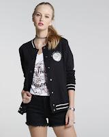 Jaqueta possui modelagem estilo college, mangas longas em tom contrastante, punhos, gola e barrados em malha canelada