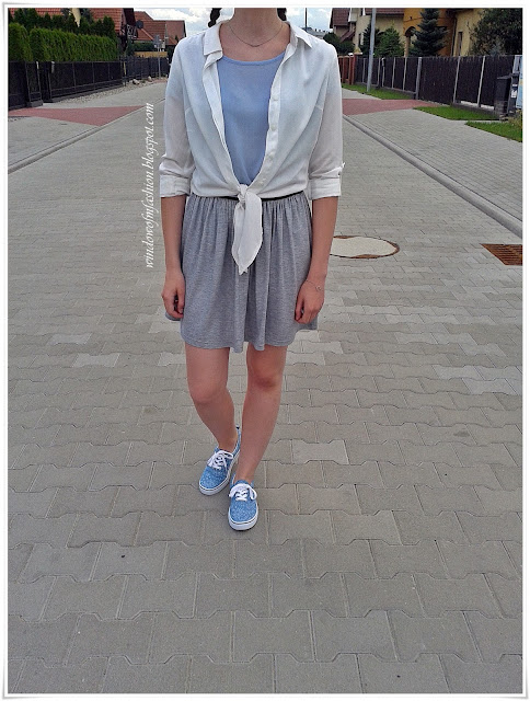 Biała wiązana koszula, niebieska bluzka, szaro-srebrna spódniczka, niebieskie tenisówki, srebrna biżuteria