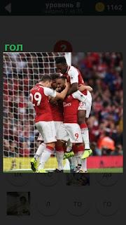 Футболисты радуются забитому голу около ворот, обнимаясь друг с другом