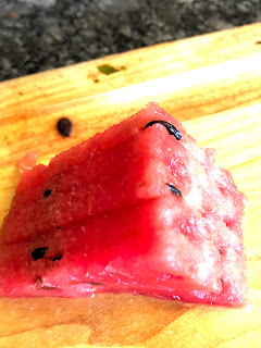 a triangle piece of red watermelon with black seeds sitting on a light colored wood cutting board