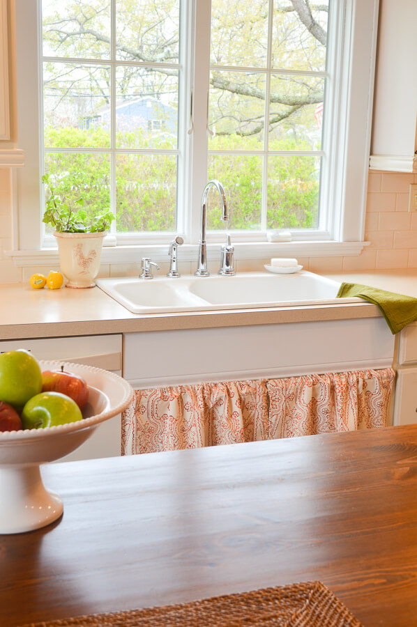 Cottage style kitchen sink area with red and white sink skirt and plants.