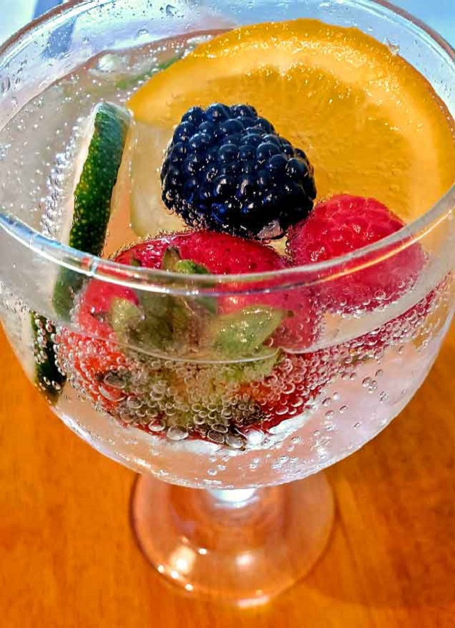 this is sparkling water with strawberries, lemon, blackberries and red raspberries in the glass