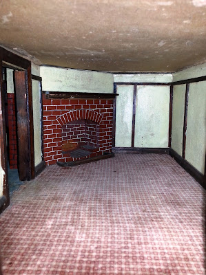 Inside view of a 1930s vintage dolls' house bungalow showing a red brick corner fireplace and dark wooden beading.