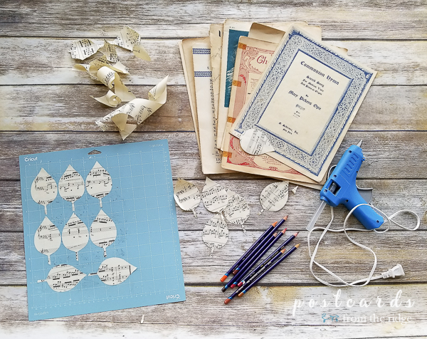 vintage sheet music and glue gun with leaves cut by cricut machine