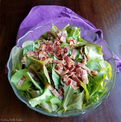 big bowl of leaf lettuce topped with chopped bacon